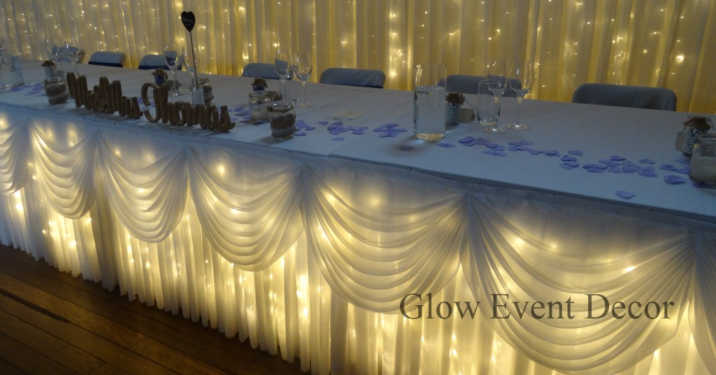 Bridal table twinkle fairy lights with draping and scalloping with fairy light bridal backdrop, wedding reception table decoration centrepieces for hire Glow Event Decor Adelaide