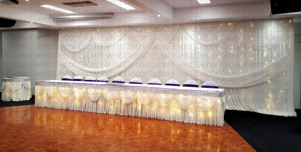 freestanding swagged fairy light wedding bridal table backdrop with matching swagged fairy light wedding bridal table skirt for hire Adelaide South Australia Glow Event Decor watermarked