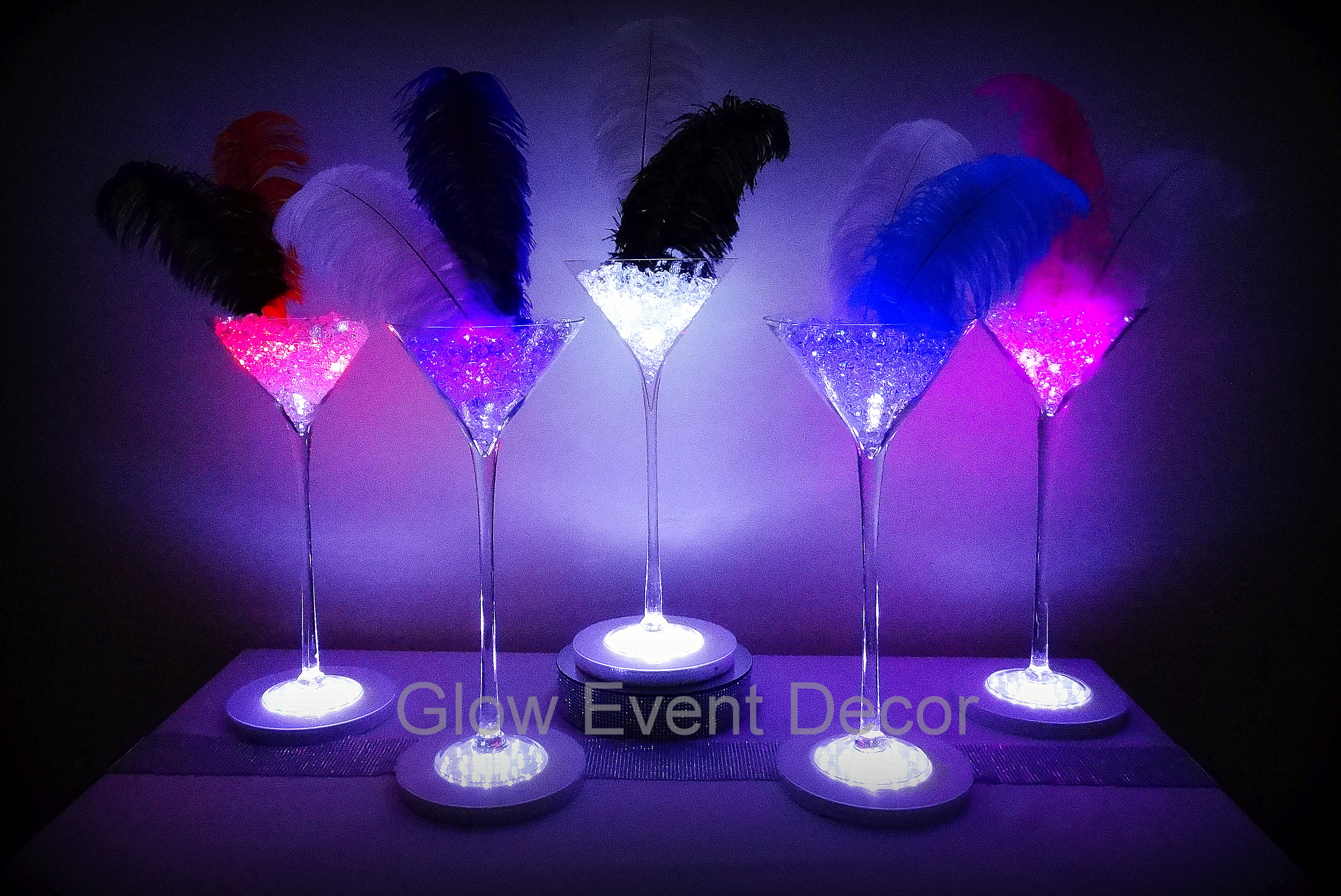 selection of LED giant martini glass table decoration centrepieces with LED light bases and ostrich feathers for hire in adelaide, glow event decor