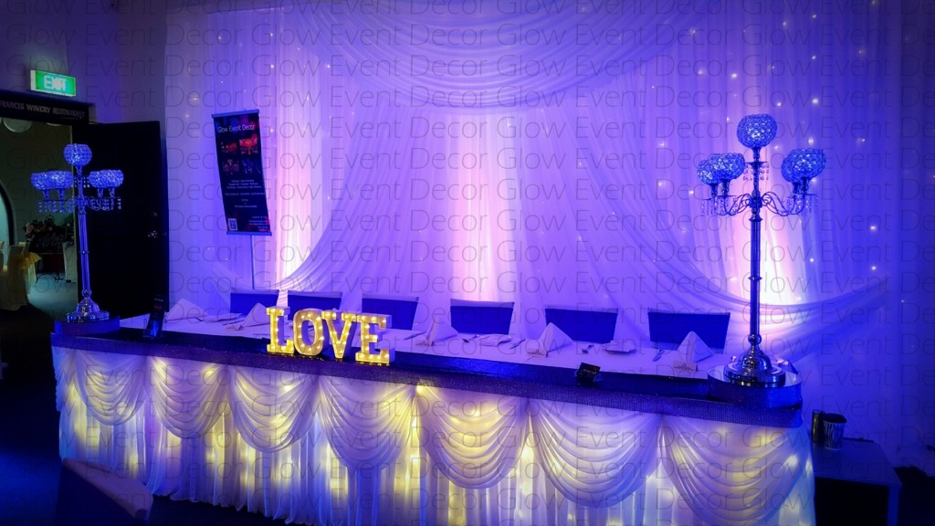 swagged backdrop with fairy lights and purple LED wall wash uplighting water marked