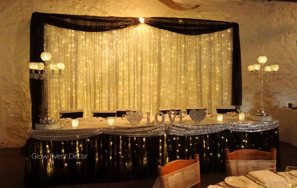 Silver sequinned backdrop with fairy lights, and black swagging, with matching black bridal table sk