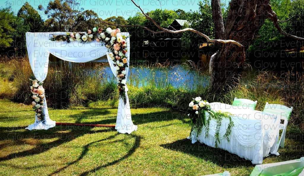 sqaure wooden arch with white draping and greenery floral swagging signing table with swagged skirt and greenery swag